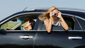 Woman leaning out of car photographing Royalty Free Stock Photos