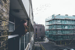 Woman leaning over balcony in city Royalty Free Stock Photo