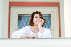 The woman is leaning on parapet outside his home Stock Photo