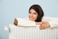 Woman leaning on radiator Stock Photography