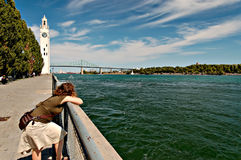 Woman leaning on rail overlooking the st lawrence. River, montreal, QC stock image