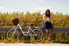 Woman Leaning on Rail Beside White Bicycle