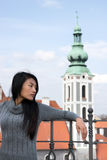 Woman leaning on a railing. Young woman leaning on a railing in the center of Cesky Krumlov Stock Photos