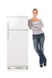 Woman Leaning On Refrigerator Over White Background. Full length portrait of young woman leaning on refrigerator over white background stock photos