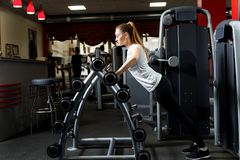 Woman leaning on a stand of barbells in a gym. stock photos
