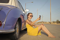 Woman leaning to a car. In yellow dress Royalty Free Stock Images