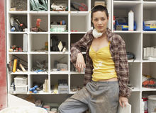 Woman Leaning On Tool Shelves. Portrait of young woman leaning on tool shelves Stock Photos
