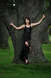 Woman leaning on tree. Woman in long black dress, leaning against a large tree with arms outstretched Stock Images