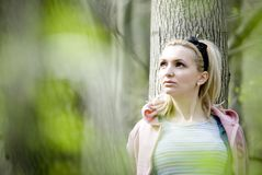 Woman leaning on tree Stock Photography