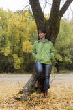 Woman leaning on a tree in a park with yellow leaves falling from trees Royalty Free Stock Photography