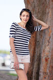 Woman leaning on a tree Royalty Free Stock Image