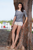Woman leaning on a tree Stock Photography