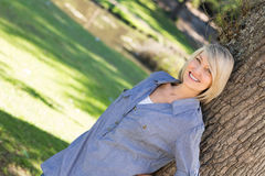 Woman leaning on tree trunk in parkland Stock Image