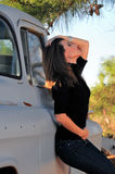 Woman Leaning on Truck. Beautiful brunette leaning on an old pick up truck Stock Photos