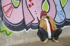 Woman leaning on a wall. Female crouched down and smiling in front of a wall covered with graffiti Royalty Free Stock Image