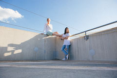Woman Leaning on Wall While Woman Wearing Shorts Sitting on Wall during Daytime Stock Photo