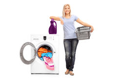 Woman leaning on a washing machine. Full length portrait of a young woman holding an empty basket and leaning on a laundry detergent on top of a washing machine stock photos