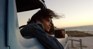 Woman leaning on window of pickup truck at beach 4k