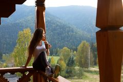 Woman leaning on wooden handrail and enjoys and relaxes beautiful mountain scenic. Young female on terrace sitting on Stock Image