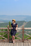 Woman leaning on wooden handrail. Woman leaning on handrail and looking away on the background of the mountainscape stock photos