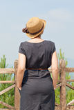 Woman leaning on wooden handrail. Woman leaning on handrail and looking away on the background of the mountainscape stock image
