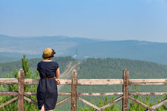 Woman leaning on wooden handrail. Woman leaning on handrail and looking away on the background of the mountainscape royalty free stock image