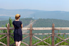 Woman leaning on wooden handrail. Woman leaning on handrail and looking away on the background of the mountainscape stock images