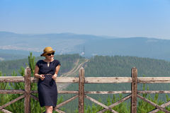 Woman leaning on wooden handrail. Woman leaning on handrail and looking away on the background of the mountainscape stock photography