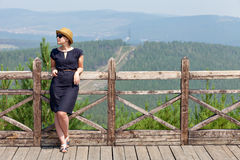 Woman leaning on wooden handrail. Woman leaning on handrail and looking away on the background of the mountainscape royalty free stock images