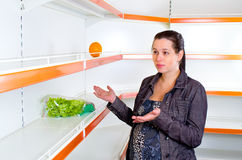 Woman leans against empty shelves in shop Royalty Free Stock Photos