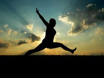 Woman Leaping. Against gorgeous sunset Stock Photos