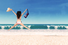 Woman leaping with bag and hat Stock Image