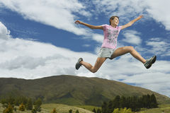 Woman Leaping On Rural Landscape Stock Image