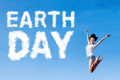 Woman leaps with Earth Day text Royalty Free Stock Image