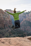 Woman Leaps High in front of vast canyon. In late afternoon royalty free stock photo