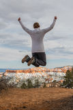 Woman Leaps for Joy at Edge of Bryce Canyon. In Winter stock photography