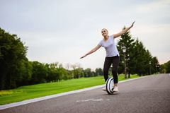A woman learn how to ride a monocycle. She tries to keep her balance. She learns to ride in the park avenue. Against the background of trees Royalty Free Stock Images