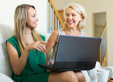 Woman learnig to use laptop from girl Stock Photography