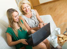 Woman learnig to use laptop from girl. Happy smiling senior women learnig how to use laptop from young girl. Focus on young Stock Photos