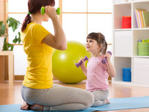 Woman learning child doing fitness exercises with dumbbells Royalty Free Stock Image