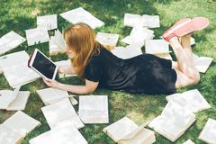 Woman learning with ebook reader and book. Choice between modern educational technology and traditional way method. Girl holding d royalty free stock images