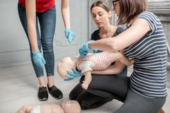 First aid training. Woman learning how to make chest compressions on a baby dummy during the first aid group training indoors royalty free stock images