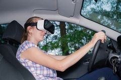 Woman learning to drive with virtual reality glasses. Young female driver using virtual reality glasses in car interior Royalty Free Stock Images