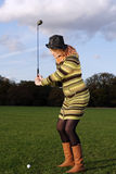 Woman learning to play golf. Woman with hat learning to hit  golfball  outdoors Royalty Free Stock Photo