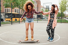 Woman learning to ride skateboard Stock Photos