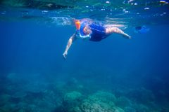 Woman learns to snorkel in full face mask. Underwater coral landscape and snorkel. Female swimmer in snorkeling mask. Woman learning to swim. Tropical vacation Stock Image