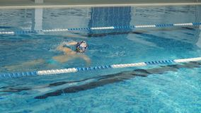 A woman learns to swim with a crawl in a covered pool. stock footage