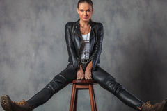 Woman in leather clothes and boots stretching her legs. Young woman in leather clothes and boots stretching her legs while sitting on stool in studio Royalty Free Stock Photo