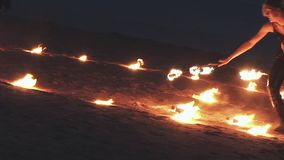 Woman in leather clothes perform fire show at beach inside burning circle. Party in nightclub. stock footage