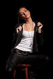 Woman in leather clothes is pulling her collar and sits. Sexy provocative young woman in leather clothes is pulling her collar and sits on a stool chair on black Stock Photography